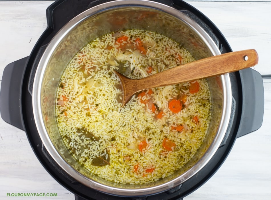over head of adding rice to Instant pot chicken soup recipe