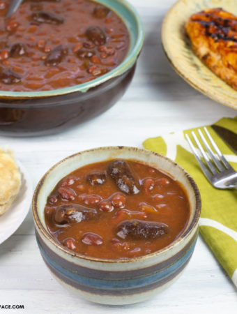 A serving bowl of Crock Pot Cowboy Beans in a small serving bowl on a table with a plate of grilled chicken, corn and a biscuit.