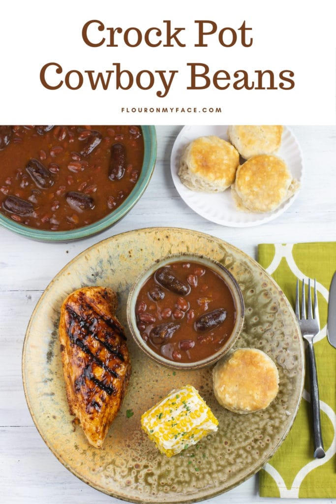 A plate with grilled chicken, corn, biscuit and a small serving bowl of Crock Cowboy Beans