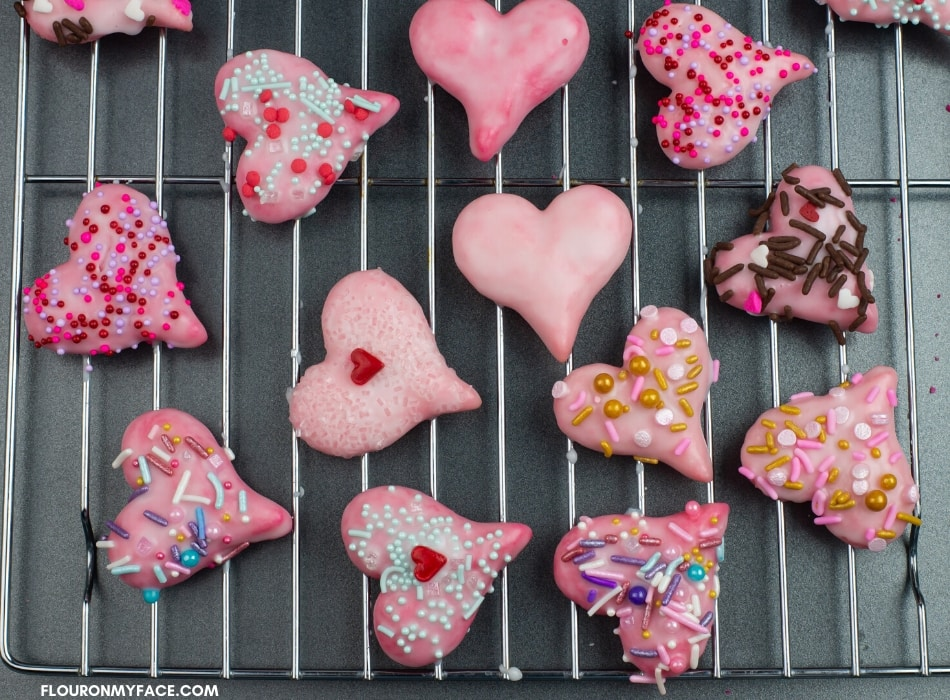 Valentines Day Spritz Cookies decorated with a sugar glaze and red, pink and gold holiday sprinkles