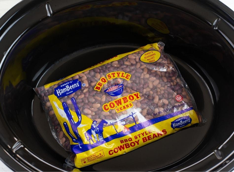 A bag of Hurst's BBQ Style Cowboy Beans inside a crock pot