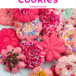 Pink Flower Spritz Cookies on a white wooden serving tray that have been decorated with icing and holiday sprinkles.