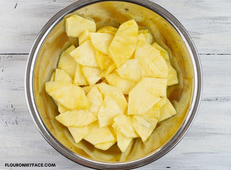 Sliced fresh pineapple slices in a large metal bowl before dehydrating