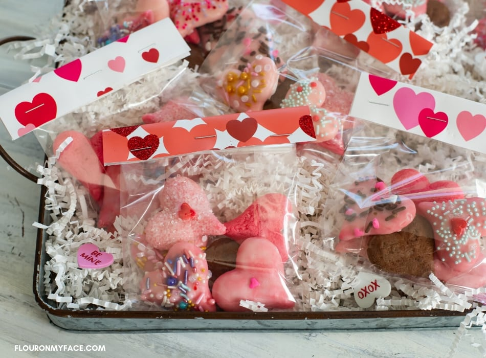 Valentines Day Spritz Cookies in treat bags on a metal serving tray.