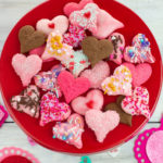 Valentines Day Spritz Cookies overhead photo with the Valentines day treats piled on a red cake stand