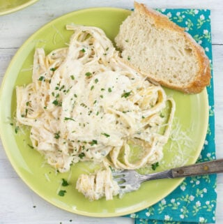 Alfredo Sauce made with half and half on a dinner plate with a slice of crusty bread, cloth napkin and fork