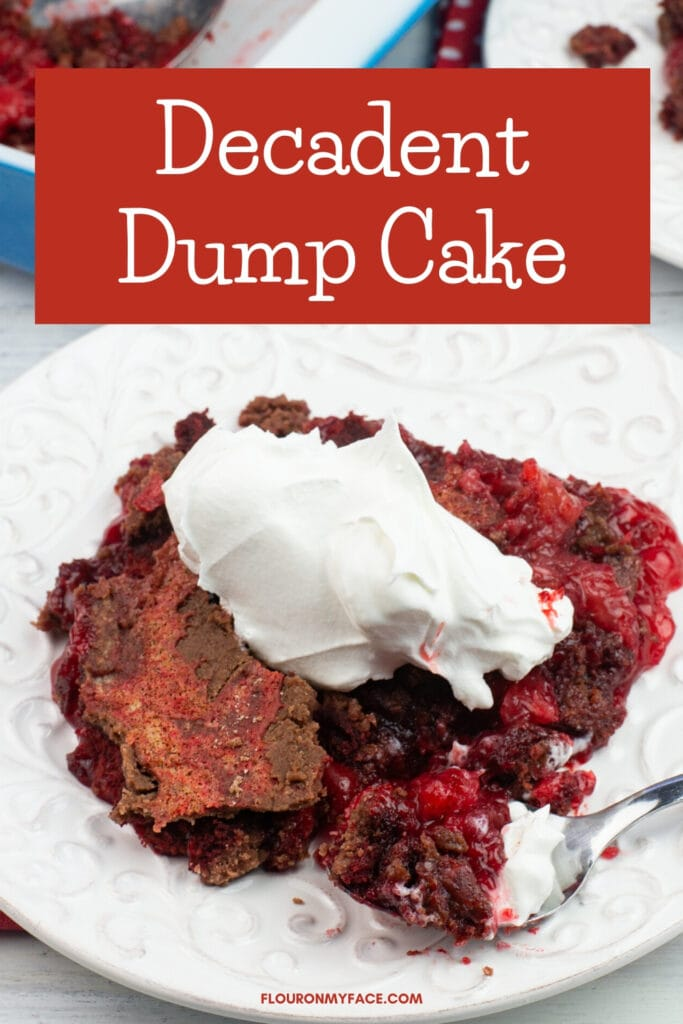 a serving of dump cake made with red velvet cake on a plate topped with whipped cream