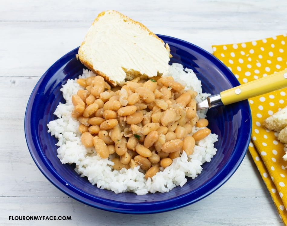 Pressure cooked great northern beans served over white rice, with a slice of buttered bread in a blue bowl