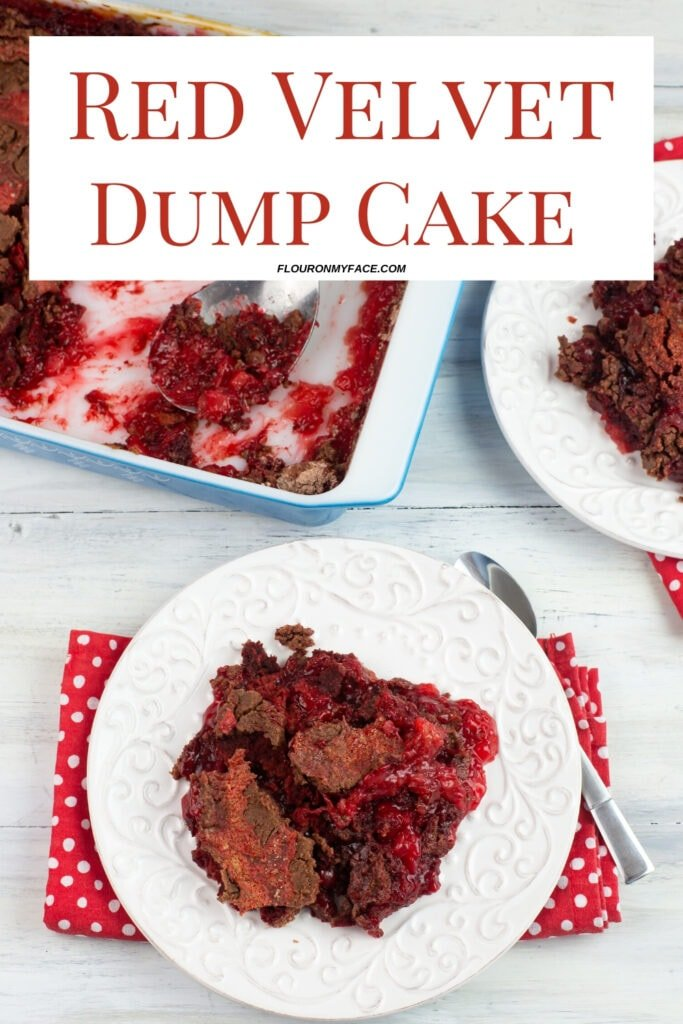 a serving of Red Velvet Dump Cake recipe on a white dessert plate with a red and white polka dot cloth napkin. The baking dish visible in the background.