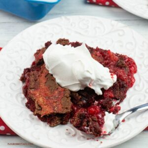 A serving of red velvet dump cake topped with whipped cream.