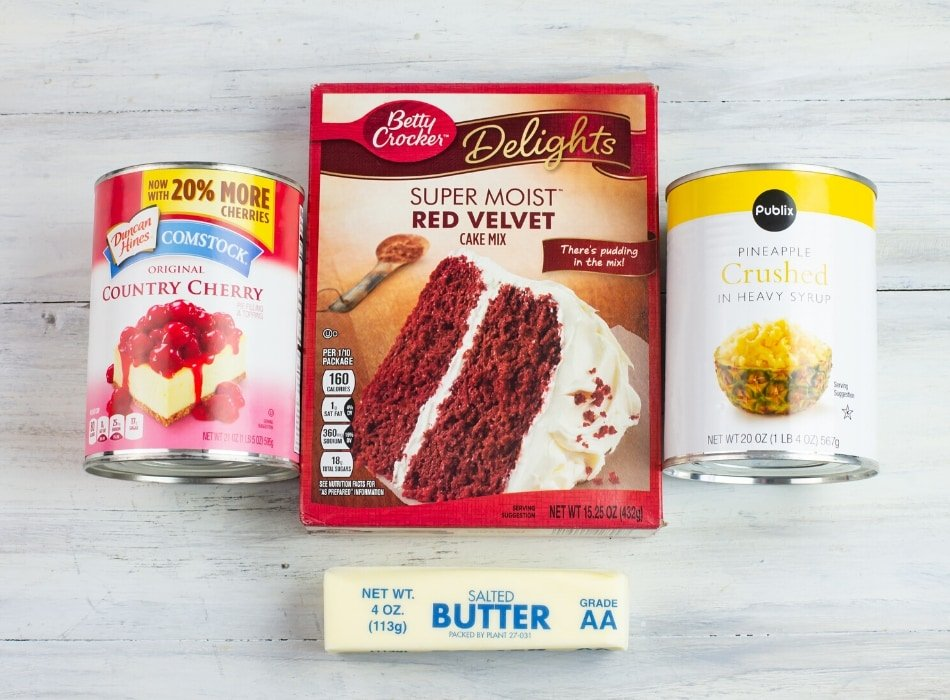 red velvet dump cake ingredients, a box of red velvet cake mix, a stick of butter, a can of cherry pie filling and a can of crushed pineapple
