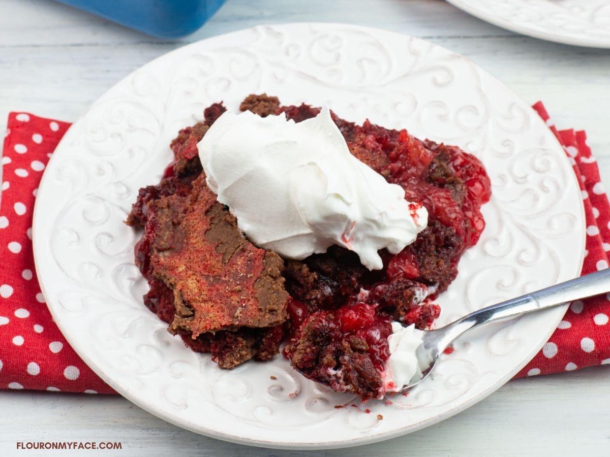 Serving red velvet dump cake topped with whipped cream on a dessert plate.