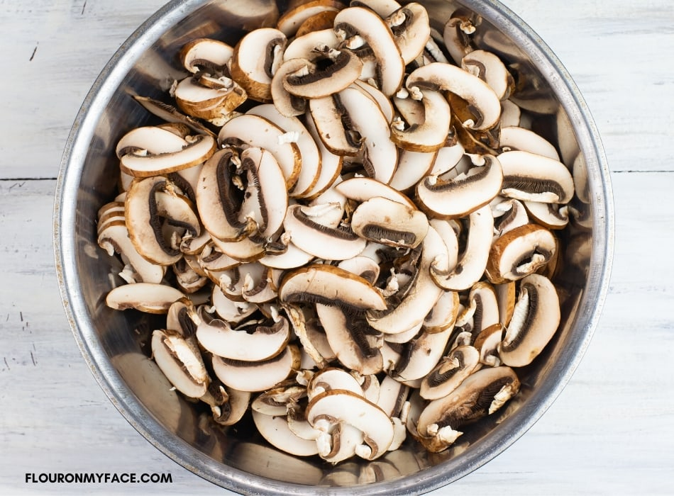 overhead photo of a metal bowl with sliced mushrooms