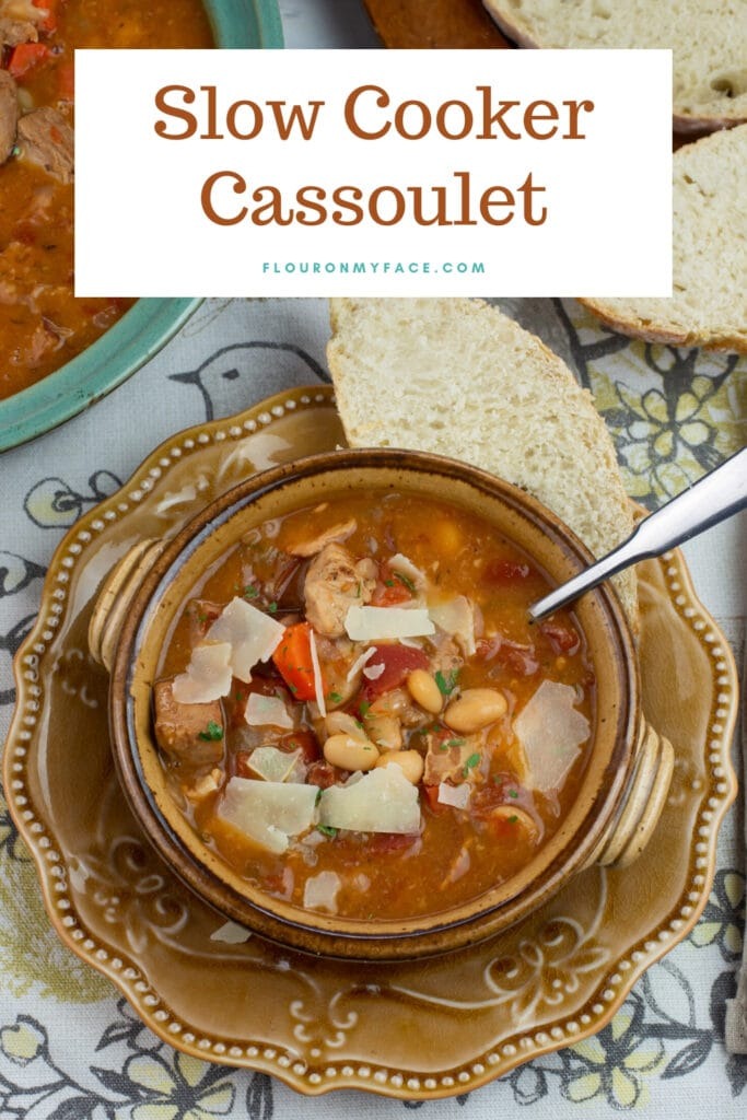 slow cooked Cassoulet in a brown crock served with rustic bread.