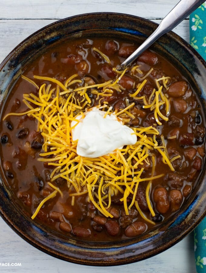 A bowl of Turkey Chili topped with shredded cheese and sour cream