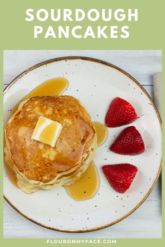 a plate with a stack of pancakes with a pat of butter and syrup drizzled over the top