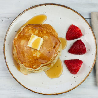 Sourdough Pancakes with a pat of butter drizzled with syrup a plate with sliced strawberries