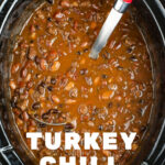 overhead photo of a crock pot filled with cooked turkey chili recipe