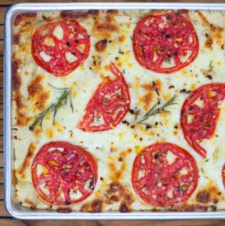 Overhead, closeup photo of a freshly baked Cheese Tomato Sourdough Focaccia