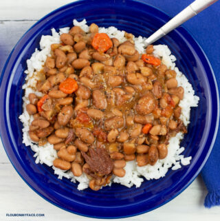 Crock Pot Pinto Beans served over white rice in a blue bowl with a blue cloth napkin