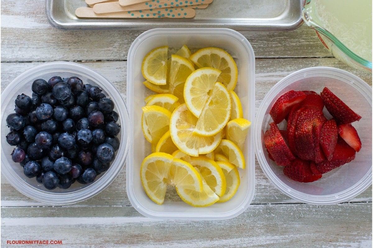 fresh blueberries, lemon slices and sliced strawberry prepared to make fruit ice pops.