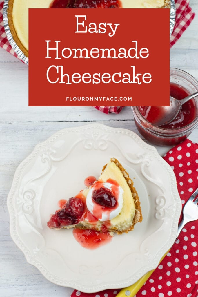a slice of homemade cheesecake on a plate with strawberry topping and whipped cream.