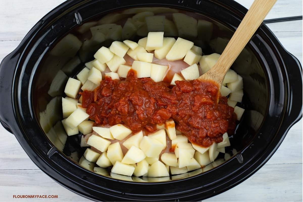Boneless chicken, cubed red potatoes and diced tomatoes in a slow cooker