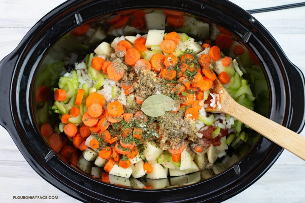 Stew ingredients in a slow cooker before adding the broth and slow cooking