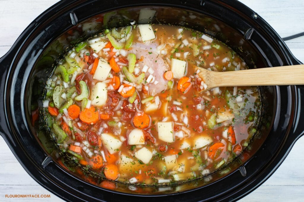 slow cooker chicken stew ingredients in chicken broth before cooking