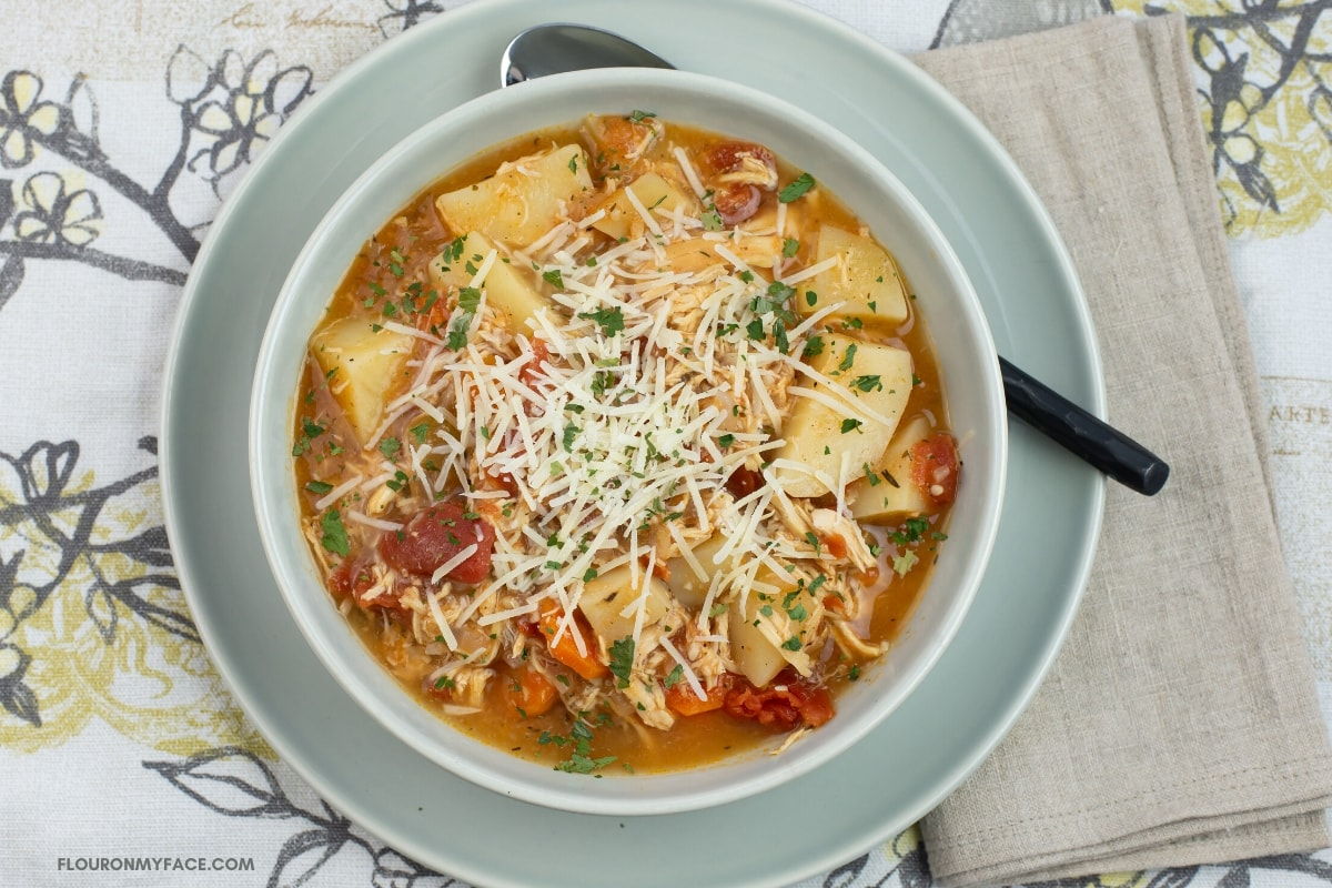 Chicken Parmesan Stew Recipe in a grey soup bowl on a saucer on a place mat with a cloth napkin