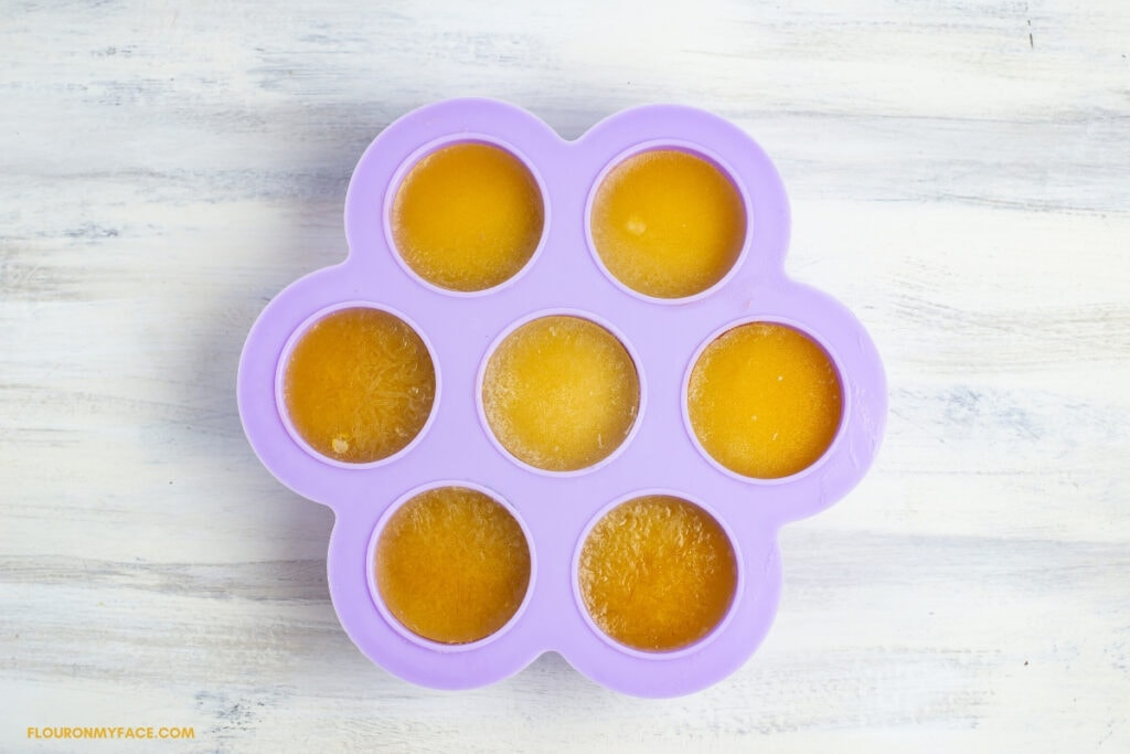 an purple silicone egg bites mold filled with frozen cubes of carambola juice.