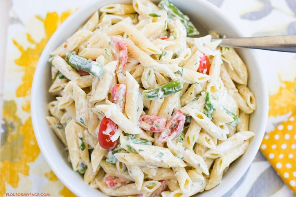 Summer pasta salad made with summer vegetables in a white bowl