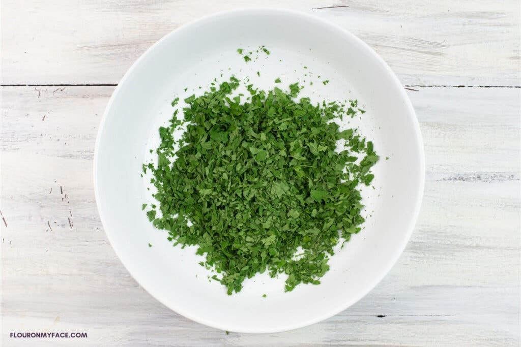 crushed dried parsley leaves in a white bowl before storing