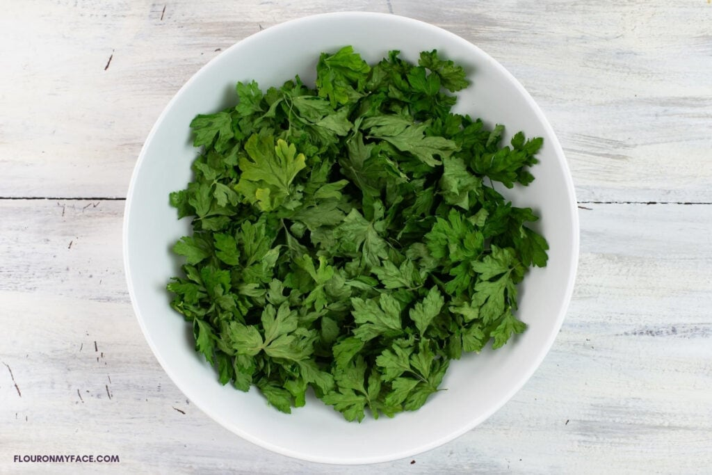 dried parsley leaves in a white bowl before crushing and storing