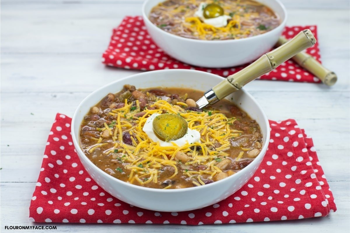 crock pot tex mex 15 beans soup in a bowl topped with shredded cheese, sour cream and jalapeno pepper slice