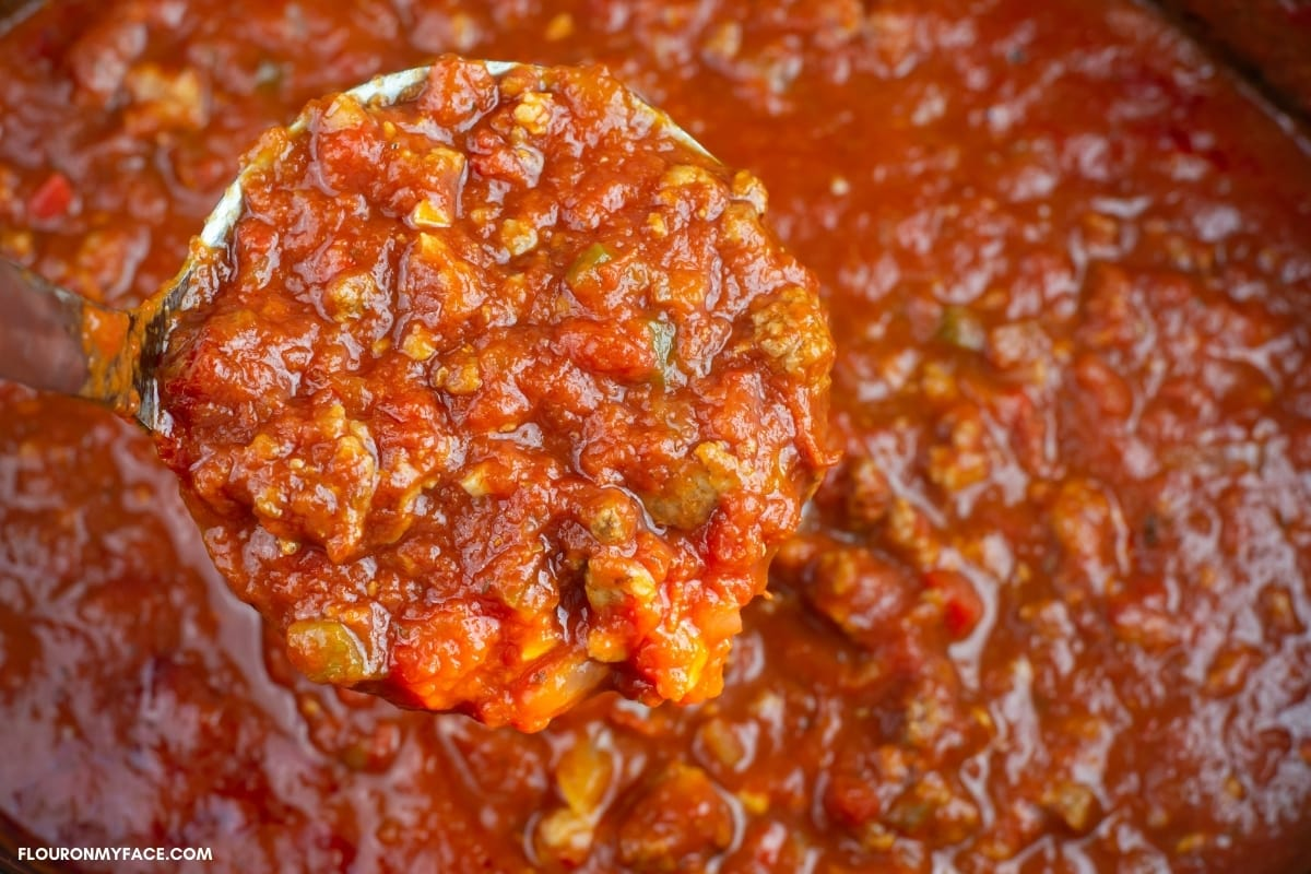Close up of a ladle full of crock pot meat sauce