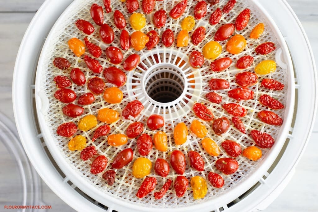 Grape tomatoes that have been cut in half and arranged in a single layer on a dehydrator tray.