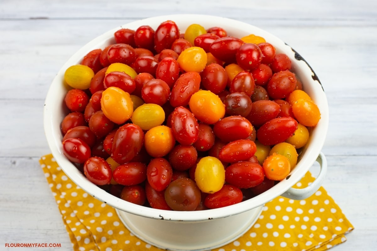 white colander filled with ripe heirloom grape tomatoes.