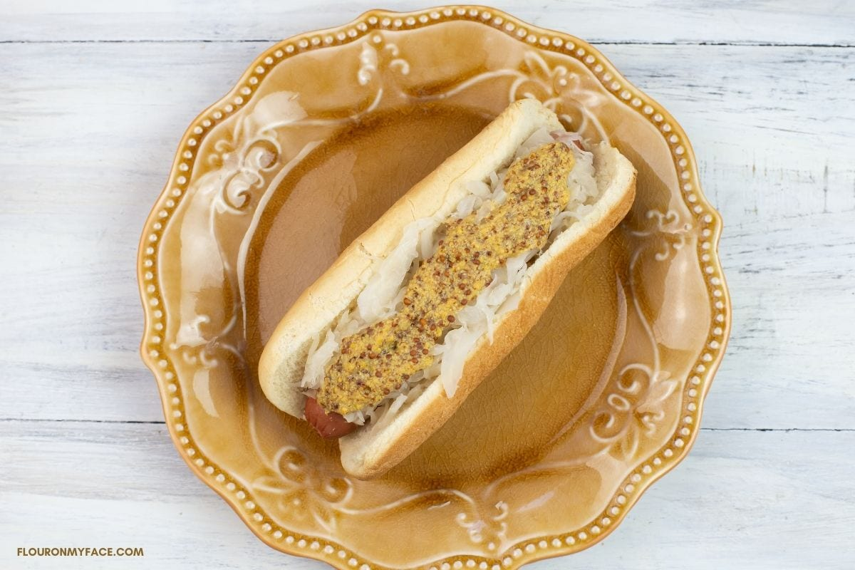 Hot dog on a bun covered with sauerkraut and slathered with grainy mustard