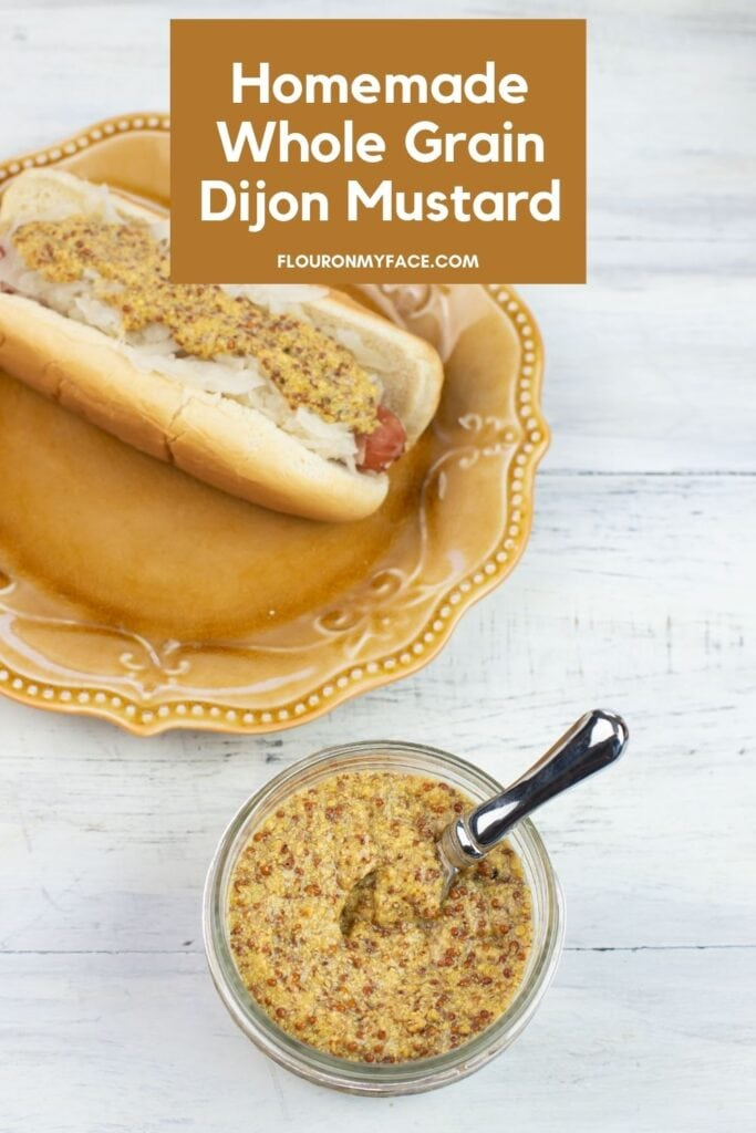 An open jar of grainy Dijon mustard and in the background is a small plate with a hot dog on a bun topped with sauerkraut and mustard