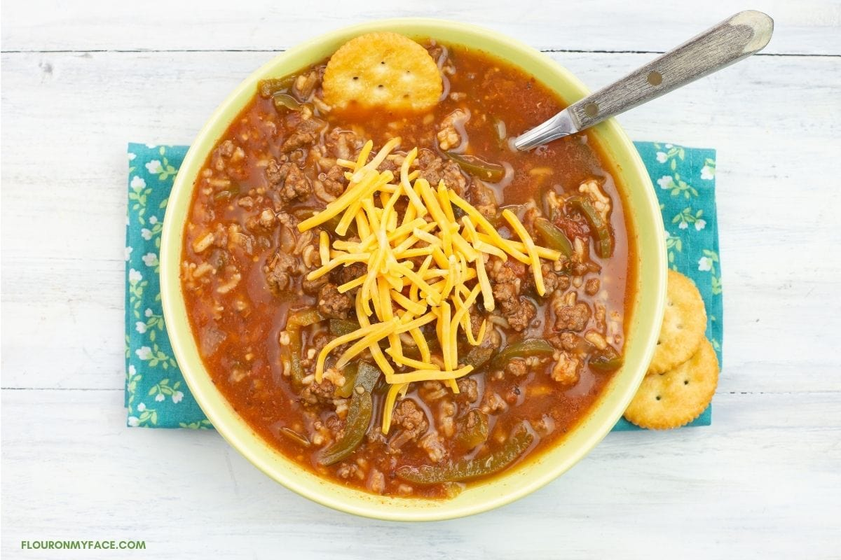 Overhead photo of a green bowl filled with Instant Pot Stuffed Pepper Soup on a cloth napkin, a spoon and cracker in the bowl, topped with shredded cheddar cheese