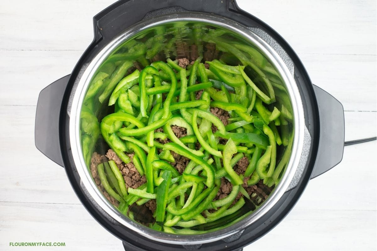 sliced bell peppers and ground beef in a pressure cooker