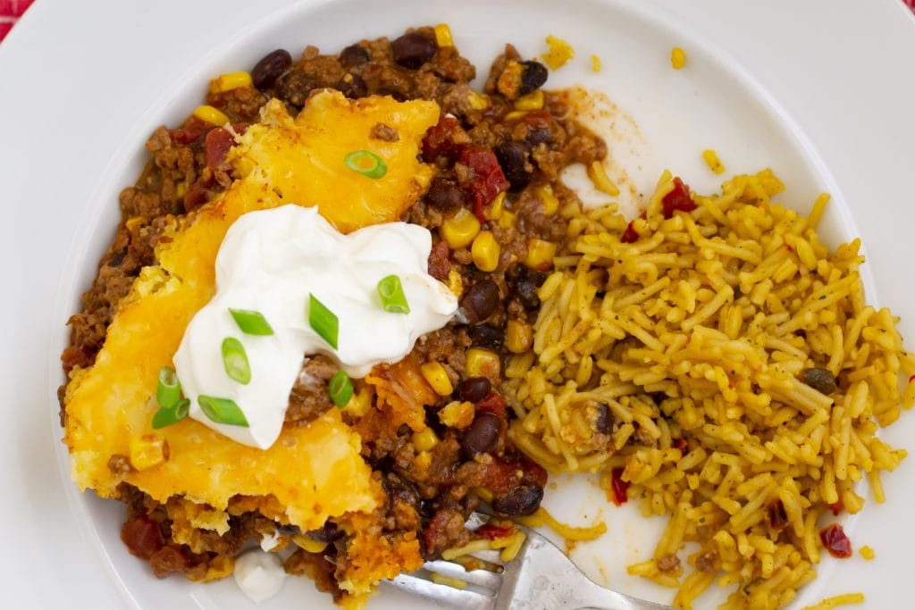 A serving of Tamale Pie and yellow Spanish rice on a dinner plate