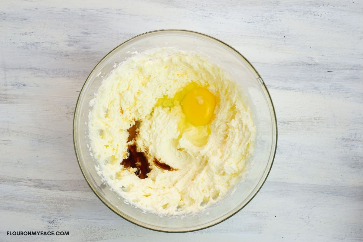 An egg and vanilla extract added to bowl of creamed butter and sugar.