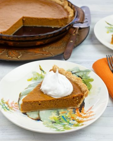 A slice of Pumpkin Pie topped with whipped cream on a dessert plate. on a pl