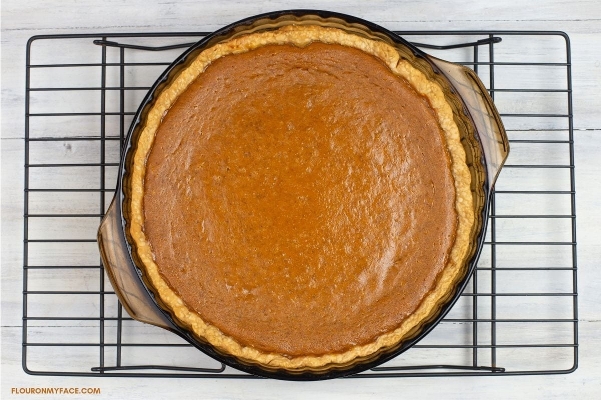 Freshly baked pumpkin pie cooling on a wire rack.