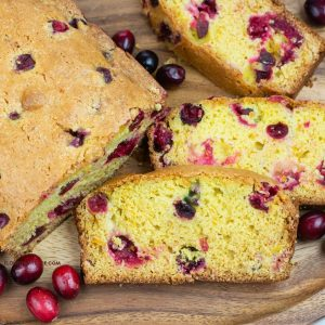 Cranberry bread slices on a wooden cutting board.