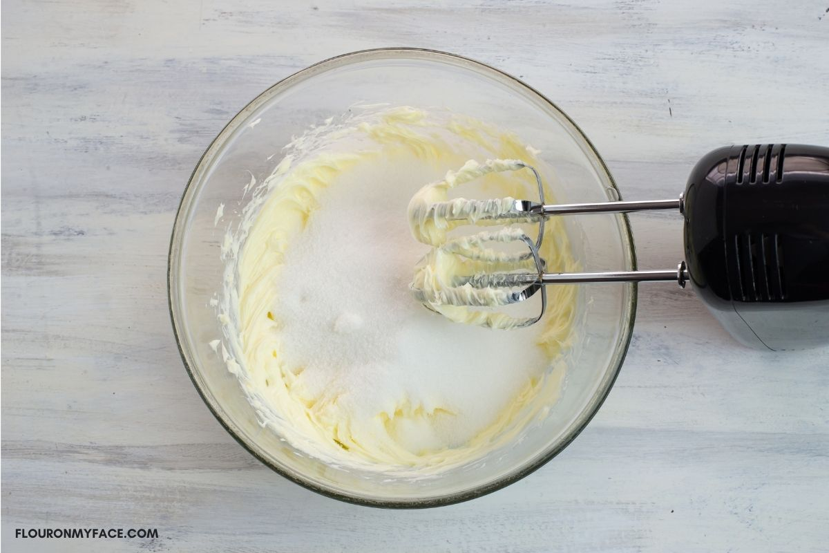 Overhead photo of a glass bowl with creamed butter and sugar.