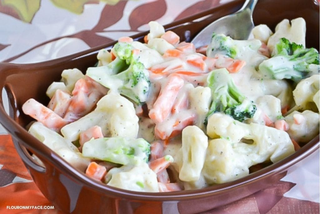 Mixed cauliflower, broccoli and carrots with a cream sauce served in a brown serving bowl.
