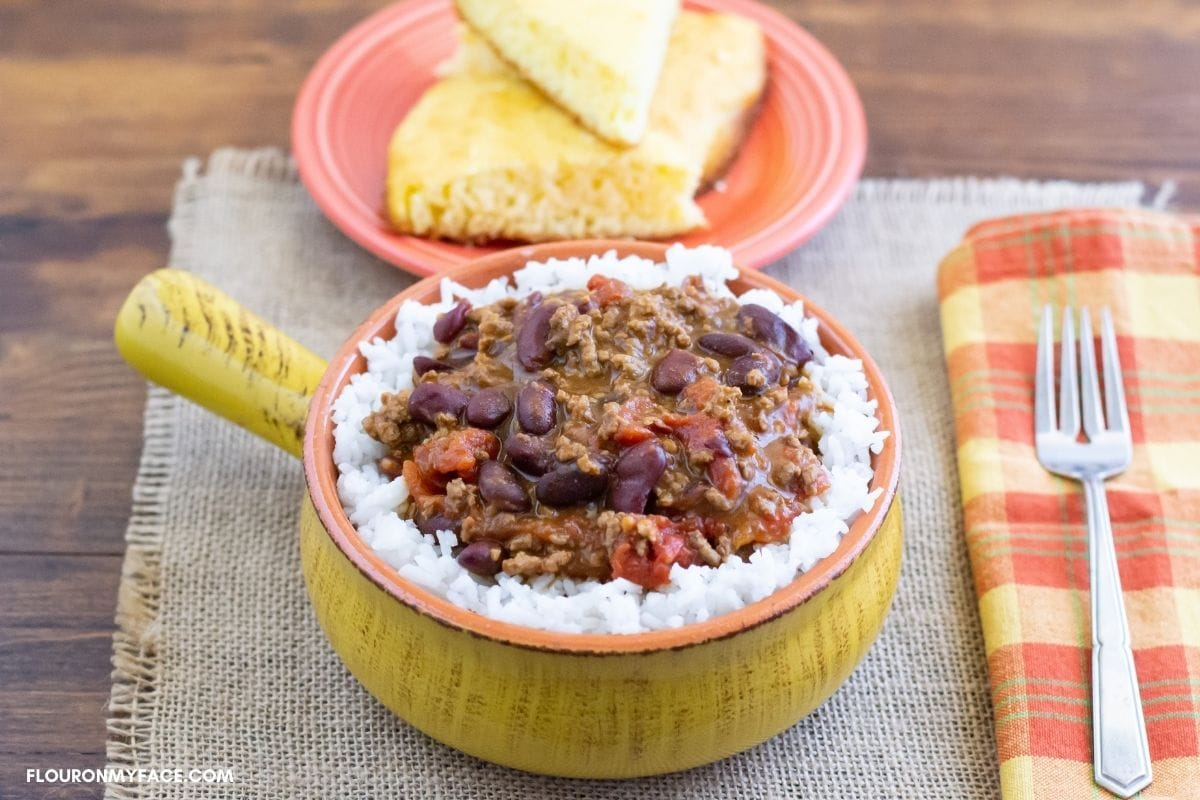 A bowl of chili over rice.